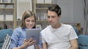Internet joven de la ojeada de los pares en la tableta mientras que se relaja en el sofá metrajes