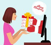 Internet Marketing concept. Beautiful woman pick up a present of Santa Claus hands from computer monitor Stock Image