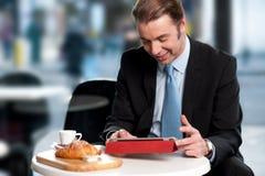 Internet masculino de la ojeada del encargado en el dispositivo de la tableta imagenes de archivo