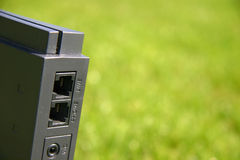 Internet modem on green grass. With closeup on phone and line ports Stock Photo