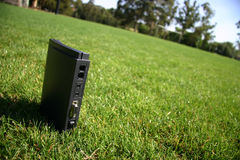 Internet modem on green grass. Outside, showing connection ports Stock Photography