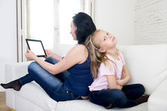 Internet network addict mother using digital tablet pad ignoring little sad daughter left alone bored Royalty Free Stock Photo