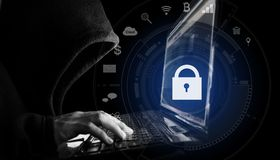Internet network security system. Hacker in black hoodie using computer laptop and technology lock and application icons stock photo