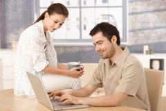 Internet novo da consultação dos pares em casa que sorri Imagens de Stock Royalty Free