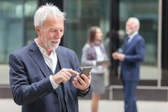 Internet o mensajería mayor feliz de la ojeada del hombre de negocios en el teléfono elegante foto de archivo
