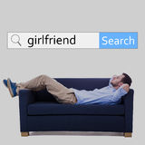 Internet and online dating concept - search bar and man lying on. Sofa and dreaming about new girlfriend Royalty Free Stock Images