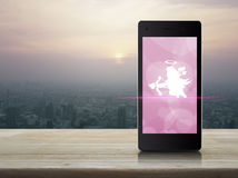 Internet online love connection. Cupid icon on modern smart phone screen on wooden table over city tower at sunset, vintage style, Internet online love royalty free stock photography