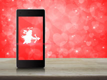 Internet online love connection, Valentines day concept. Cupid icon on modern smartphone screen on wooden table over blur red background, Internet online love royalty free stock photo