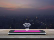 Internet online love connection, Valentines day concept. Heart wifi icon on modern smart phone screen on wooden table over blur aerial view of cityscape on warm royalty free stock image