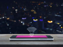 Internet online love connection, Valentines day concept. Heart wifi icon on modern smart phone screen on wooden table over blur colourful night light city tower royalty free stock photography