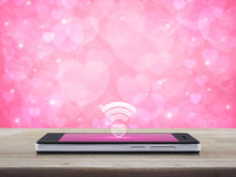 Internet online love connection, Valentines day concept. Heart wifi icon on modern smart phone screen on wooden table over blur pink background, Internet online stock image