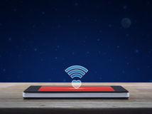 Internet online love connection, Valentines day concept. Heart wifi icon on modern smart phone screen on wooden table over fantasy night sky and moon, Internet stock images