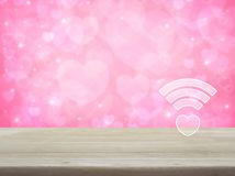 Internet online love connection, Valentines day concept. Heart wifi icon on wooden table over blur pink background, Internet online love connection, Valentines stock photo