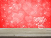 Internet online love connection, Valentines day concept. Heart wifi icon on wooden table over blur red background, Internet online love connection, Valentines royalty free stock photo
