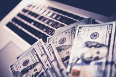 Internet Online Scam Money. Internet Scam Money. Earned Dollars From Cyber Crime Conceptual Photo with Banknotes Laying on the Laptop Computer Stock Photo