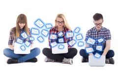 Internet-praatje - twee tieners en één jongenszitting met lapto Stock Afbeelding