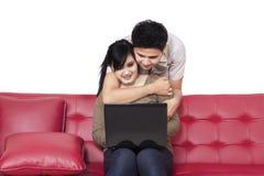 Internet praticante il surfing a casa 2 delle giovani coppie Immagine Stock
