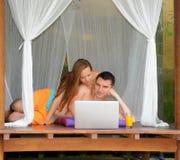 Internet praticante il surfing sorridente felice delle coppie Immagine Stock Libera da Diritti