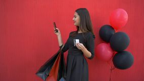 Internet purchases, happy smiling girl makes online shopping using mobile phone and electronic money in black Friday. Seasonal sale on background red wall stock video