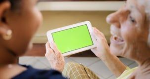 Internet que practica surf de la abuela y de la chica joven con la tableta fotografía de archivo