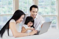 Internet que practica surf de la familia asiática Imágenes de archivo libres de regalías