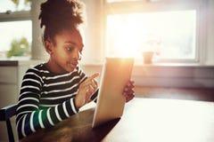 Internet que practica surf de la muchacha afroamericana usando la tableta Foto de archivo libre de regalías
