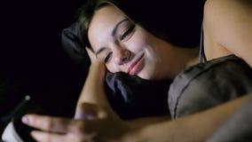 Internet que practica surf de la muchacha mientras que miente en cama en el dormitorio en la noche, mira la foto, chating y sonri almacen de metraje de vídeo