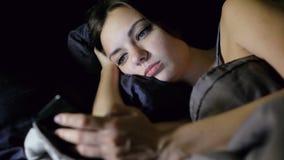 Internet que practica surf de la mujer mientras que miente en cama en el dormitorio en la noche, mira la foto, chating metrajes