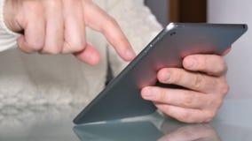 Internet que practica surf del hombre adulto joven con su tableta almacen de metraje de vídeo