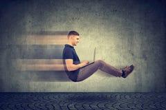 Internet rápido Elevar y mantener flotando al hombre de negocios en el camino usando el ordenador portátil imagenes de archivo