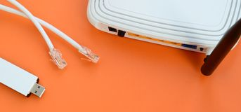 Internet router, portable USB wi-fi adapter and internet cable p. Lugs lie on a bright orange background. Items required for internet connection royalty free stock images