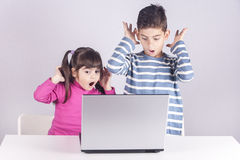 Internet safety for kids concept. Little kids react with shock and awe while using a laptop. Internet safety for kids concept Royalty Free Stock Photo