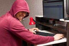 Internet-Schleppangel mit dem schlechten Gesicht unter Verwendung eines Computers Sehr lacht böser Mann böse Sachen auf das Forum Stockfoto
