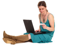 Internet shopping. Woman sitting on the floor with laptop and credit card (Magnetic stripe showing Stock Photos