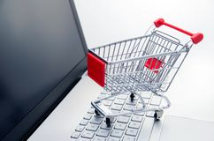 Internet shopping concept. Basket on laptop keyboard Royalty Free Stock Photography