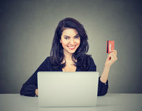 Internet shopping and payment. Woman showing credit card using laptop computer. Internet shopping and payment concept. Smiling happy young woman showing credit Royalty Free Stock Photo