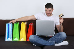 Internet shopping with shopping bags. A young man with shopping bags is using his laptop computer for internet shopping Royalty Free Stock Photos