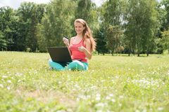 Internet shopping woman online with laptop and credit card sitting outdoor on green grass. Royalty Free Stock Images
