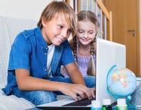 Internet sonriente de los niños que charla en el cuaderno Imagenes de archivo