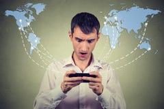 Internet sorpreso di lettura rapida collegato smartphone della tenuta dell'uomo Fotografia Stock Libera da Diritti