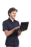 Internet sorridente di lettura rapida dell'uomo sul computer portatile Fotografia Stock Libera da Diritti