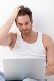 Internet sportif de furetage d'homme sur l'ordinateur portatif Photos stock