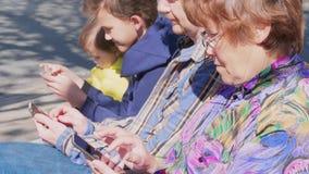 Internet-Sucht, -erwachsene und -kinder mit den Mobiles im Freien stock video