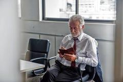 Internet supérieur d'Using d'homme d'affaires au téléphone intelligent Photographie stock