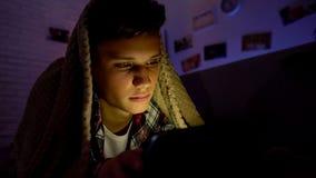 Internet surfando do adolescente cansado na aba em vez do sono, encontrando-se sob a cobertura imagem de stock