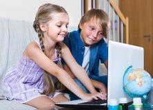 Internet surfando ordinário de sorriso das crianças fotografia de stock
