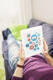 Internet surfant avec le comprimé numérique sur le divan Photographie stock libre de droits