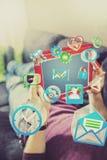 Internet surfant avec le comprimé numérique sur le divan Image stock
