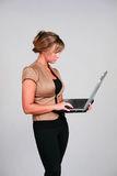 Internet Surfer. Beautiful young female in business clothes holding a laptop computer Stock Photo