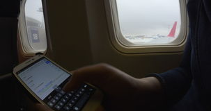 Internet surfing with smart phone in the plane stock video footage